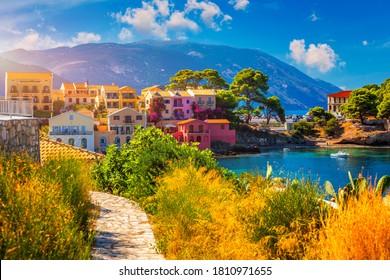 Türkisfarbene Bucht im Mittelmeer mit schönen bunten Häusern im Dorf Assos in Kefalonia, Griechenland. Stadt von Assos mit bunten Häusern auf dem Mittelmeer, Griechenland.