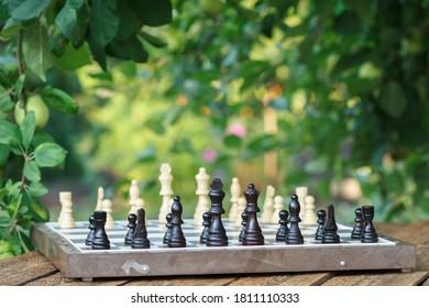 リンゴの木の枝と背景に緑の葉が付いている木製の机の上のチェスの駒とチェス盤。黒い部分に選択的に焦点を合わせます。