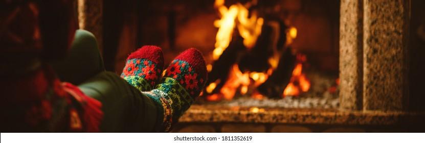 Füße in Wollsocken am Kamin. Frau entspannt sich am warmen Feuer und wärmt ihre Füße in Wollsocken auf. Während der Quarantäne zu Hause bleiben. Winter- und Weihnachtsferienkonzept. Banner-Format.