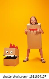 段ボールのドラゴン、恐竜と遊ぶ感情的な少女。子供の頃の夢。ファンタジー、想像力。黄色の背景にスタジオポートレート。