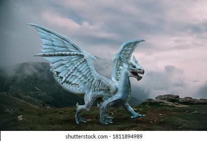 Fantasy-Drache steht auf der Spitze des Berges. Ein riesiges gefährliches Tier mit großen, scharfen Flügeln. Schöner alpiner Naturhintergrund, dramatischer grauer blauer Himmel mit weißen Wolken.
