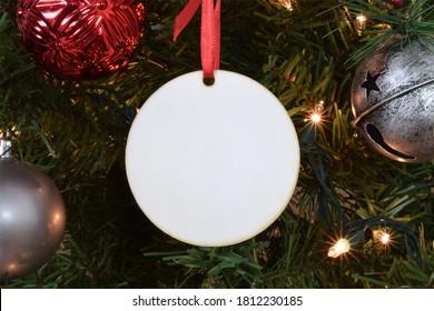 Leere runde Weihnachtsverzierung, die von einem beleuchteten Weihnachtsbaum hängt, umgeben von Verzierungen.
