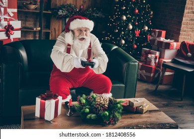 Foto von aufgeregten süchtigen grauen Haaren Santa Claus sitzen Couch feiern Weihnachten Weihnachten Nacht Mitternacht spielen Videospiel tragen rote Kappe Kopfbedeckung im Haus drinnen Newyear Ornament