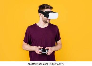 Menikmati pengalaman baru. lelaki bermain permainan video. pemain permainan dengan konsol. lelaki dalam alat dengar VR. pemain permainan menggunakan teknologi moden. Masa depan dan inovasi digital. Realiti visual. lelaki memakai cermin mata VR tanpa wayar.