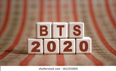 BTS 2020 text on wooden cubes on a monochrome background with reflection.