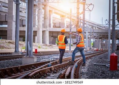 検討中のエンジニアは、建設プロセスの鉄道スイッチの検査とチェック、および鉄道駅の作業のチェックを行っています。作業中の安全ユニフォームと安全ヘルメットを着用しているエンジニア。
