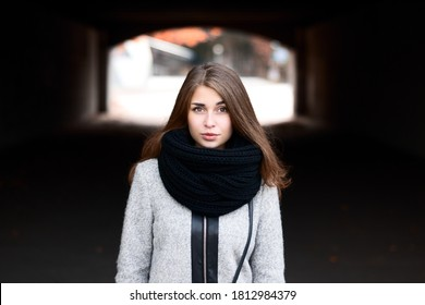 Close up portrait of beautiful girl with brown hair outdoors. Gorgeous brunette girl in coat and scarf, art portrait on the city street. Stylish fashionable young pretty beautiful girl looks in camera