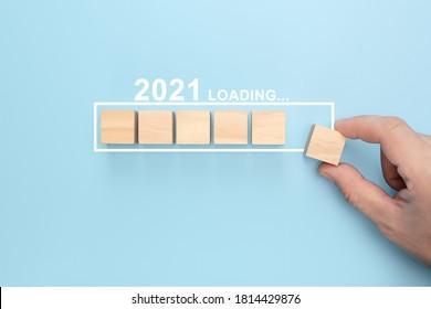 プログレスバーに木製の立方体を手で置くことで新年2021をロードします。新年の創造的な背景。新年2021コンセプトを読み込んでいます