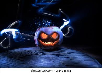 Halloween-pompoenglimlach en enge ogen voor feestavond. Close-up van enge Halloween-pompoen met ogen gloeien binnen op zwarte achtergrond. Selectieve aandacht