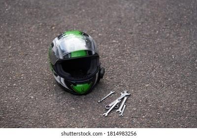 Casco de moto en el suelo y algunas llaves. Llave en el suelo