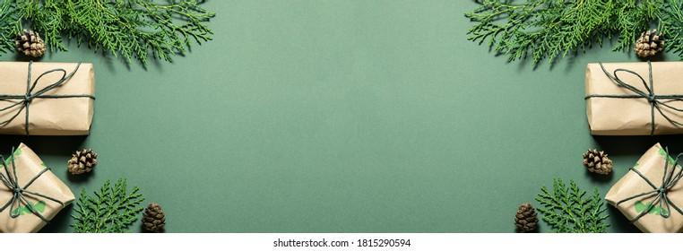 Composición navideña ecológica con cajas de regalo en papel artesanal reutilizable y decoración natural en la vista superior de fondo verde. Concepto de Navidad ecológico de cero residuos. Formato de banner largo.