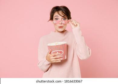 映画フィルムを見て、ニットのカジュアルなセーターの眼鏡をかけている20代の若いブルネットの女性を驚かせ、パステルピンクの背景に分離されたポップコーンのバケツを保持します。映画における人々の感情、ライフスタイルの概念。
