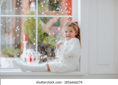 Young pretty girl with blond curly hair and red Christmas bow in white winter long dress and long socks sitting near the big window holding white small rat. Snow background.