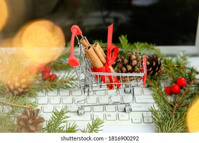 Christmas shopping and sale on the Internet.Red shopping cart with cinnamon and cones on a white background on the computer, green Christmas tree.Merry Christmas! Happy New Year!