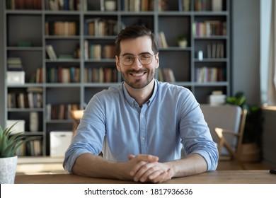 Headshot-Porträt eines lächelnden kaukasischen tausendjährigen Mannes der 30er Jahre in Gläsern sitzen am Schreibtisch zu Hause und sprechen über einen Videoanruf oder eine virtuelle Webcam-Konferenz. Bild des glücklichen jungen Mannes in der Brille, die am Tisch aufwirft.