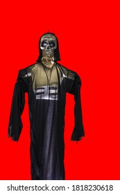 View of skeleton figure in black cloth on red background isolated.