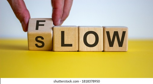 Be slow or in the flow. Male hand turns a cube and changes the word 'slow' to 'flow'. Beautiful yellow table, white background, copy space. Business concept.