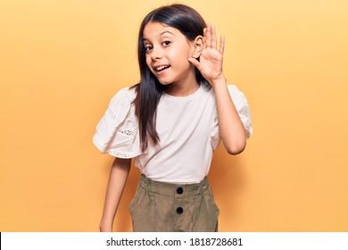 Schönes Kindermädchen, das lässige Kleidung trägt, die mit Hand über Ohr lächelnd hört und zu Gerüchten oder Klatsch hört. Taubheitskonzept.