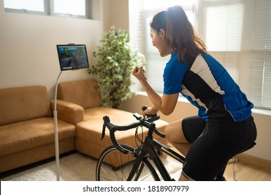 Asian woman cyclist. She is exercising in the home.By cycling on the trainer and play online bike games.She is glad