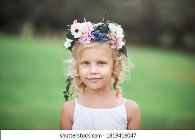 彼女の頭に花の花輪を持つ白いドレスのかわいい女の子