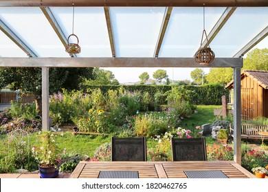 Terraza con techo de vidrio y vista al jardín