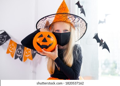 Portrait blonde girl in witch costume wearing face masks with candy bucket in coronavirus pandemic preparing for Halloween protecting from COVID-19.