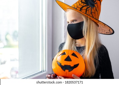 Sad thoughtful blonde girl in witch costume wearing mask looking in window at home with candy bucket. preparing for Halloween protecting from covid.