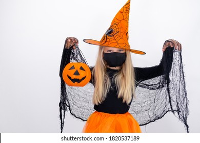 Portrait blonde girl in witch costume wearing face mask with candy bucket pumpkin preparing for Halloween on white studio background. copyspace.