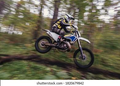 森の中でエンデューロモトクロスバイクでジャンプするドライバー
