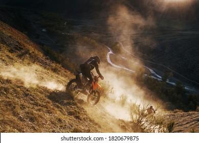 エクストリームライダーがオフロードクロスエンデューロバイクで砂山の頂上を登る。背景に美しい山々の風景、日差しの中でカラフルな秋の森と川