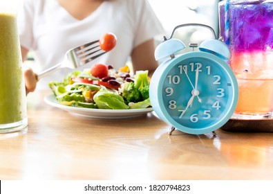 Selective focus of blue clock which woman make a Intermittent fasting with  a Healthy food of salad .Healthy lifestyle Concept.