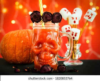 glass mug skull with red tomato juice. a cocktail at a halloween party. marshmello scary faces, ghosts. pumpkin