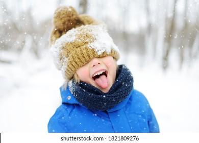 青い冬の服を着た面白い男の子が降雪の間に歩きます。子供のための屋外の冬の活動。目の下に暖かい帽子をかぶって、舌で雪をキャッチするかわいい子供