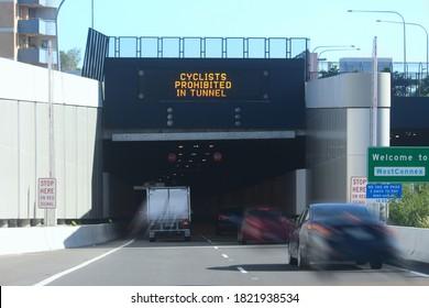 パラマッタロードからアッシュフィールドの新しいM4ウェストコネックストンネルに入る車とトラック。入り口には「トンネル内で禁止されているサイクリスト」と書かれた看板があります。制限速度は時速60kmです