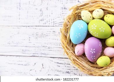 木製の背景の色に巣のイースターエッグ