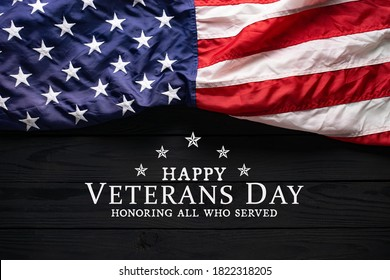 Happy Veterans Day. American flag on black wooden background with text.