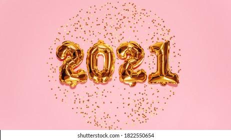 明けましておめでとうございます2021年のお祝い。明るい金色の風船の数字、ピンクの背景にキラキラ星が付いた新年の風船。クリスマスと新年のお祝い。金箔風船2021ギフトカード