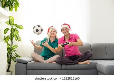 junges Paar spielt Videospiel mit Joysticks zu Hause zu Weihnachten
