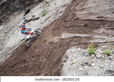オフロードエンデューロバイクで砂の採石場の山を登るライダー