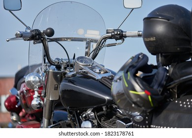 Chromen motorfiets. Voorraad. Zijaanzicht van nieuwe zwarte motorfiets met chromen details en kleding van motorrijder die erop ligt. Chromen details motorfiets weerspiegelen landschap van steppe voor reis
