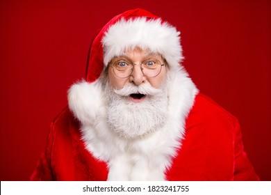 Foto de anciano jubilado barba gris boca abierta mirada emocionada ver criatura mágica de año nuevo hacer deseo traer atmósfera usar traje de santa abrigo gafas sombreros aislado color rojo fondo