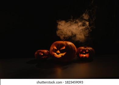 Drie griezelige halloween dampende pompoenen met een gebeeldhouwde lichtgevende grijns op een zwarte achtergrond. Een handgemaakte jack-o-lantern kop met een kaars erin in het donker tussen de mist. Snoep of je leven. Ansichtkaart.