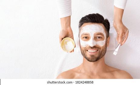 Draufsicht des bärtigen fröhlichen Mannes, der Gesichtsbehandlung am modernen Spa-Salon erhält. Weiblicher Begleiter, der weiße Gesichtsmaske auf Manngesicht mittleren Alters anwendet. Männliches Gesichtspflegekonzept, Panorama mit freiem Raum
