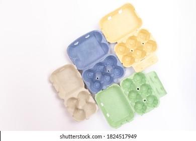Grüne, gelbe, blaue Papier-Eierbox, Fall, Halter, Paket, Draufsicht auf weißem Hintergrund, abstrakte Farbkombination