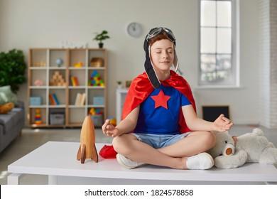Grappige kleine jongen zittend op de tafel in de lotushouding in de kinderkamer. Glimlachend kind in rode superheld cape en pilotenhelm met gesloten ogen pretendeert te mediteren.