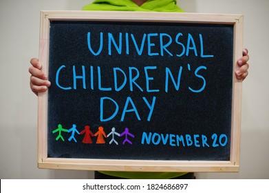 Universal children's day, November 20. Boy hold chalkboard with blue inscription.