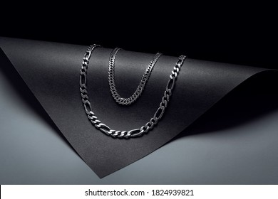double silver chain necklace on black background with dark and rounded shapes