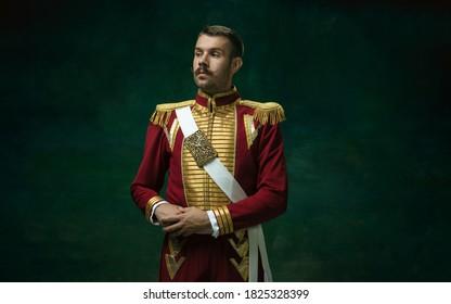 濃い緑色の背景に分離されたニコライ2世としてスーツを着た若い男。レトロなスタイル、時代のコンセプトの比較。歴史的なキャラクター、君主、昔ながらのような美しい男性モデル。