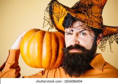 Ingredientes de cocina de temporada de Acción de Gracias. Hombre guapo con sombrero de Halloween con calabaza - retrato de cerca. Hombre joven con sombrero de bruja listo para la fiesta de Halloween