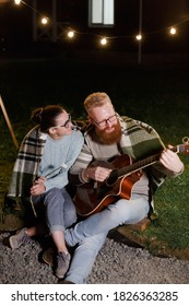 Young couple, caucasian woman and red haired bearded man, on a night picnic with a guitar and marshmello have a good time